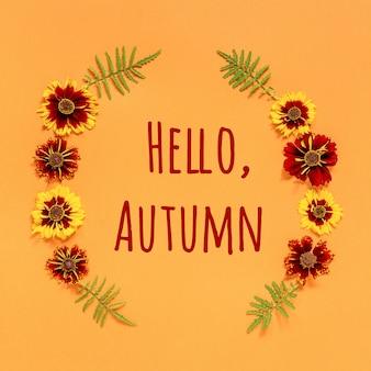 こんにちは秋のテキストとオレンジ色の背景に黄色の赤い花のフレーム。トップビューフラットレイアウトグリーティングカード招待状
