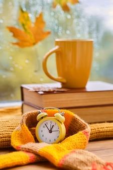 Привет осень. желтый будильник, завернутый в шарф, чашка на книгах у окна, идет дождь