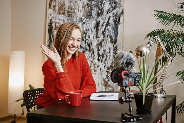 안녕하세요 아름다운 여성 블로거가 vlog용 비디오를 녹화하고 실내에 앉아 웃고 있습니다.