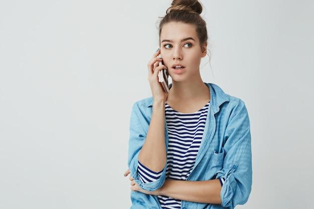 Ciao posso ordinare. il ritratto della bella donna alla moda casuale casuale che guarda da parte lo smartphone premuroso della tenuta ha premuto l'orecchio, la conversazione, prenotando il ristorante della tavola via telefono cellulare