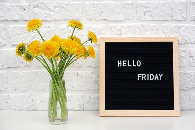 Hello friday words on black letter board and bouquet of yellow dandelions flowers