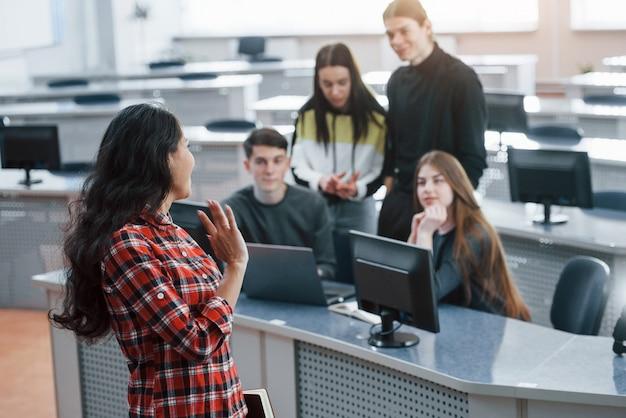 Привет, жест. группа молодых людей в повседневной одежде, работающих в современном офисе