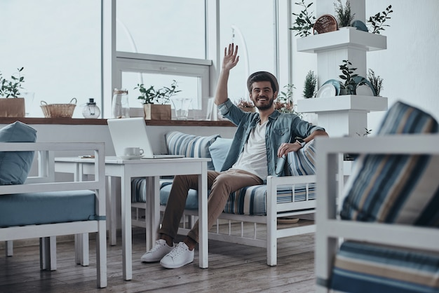 Привет! красивый молодой современный человек смотрит в камеру с улыбкой и машет рукой