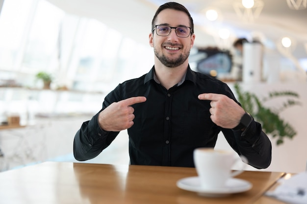 Hello, it's me! attractive cheerful man in black shirt indexing fingers on his chest and smiling. he sitting in coffeehouse and waiting for meeting with online friends.