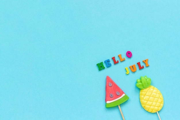 Hello july colorful text, pineapple and watermelon lollipops on blue