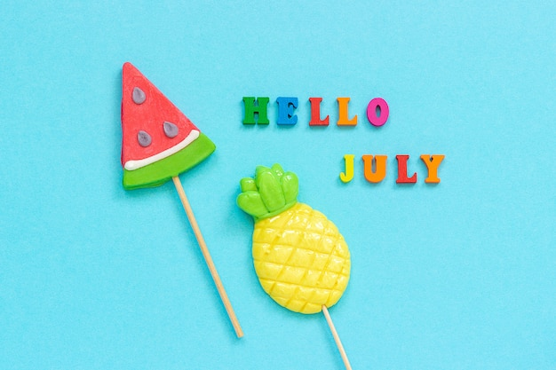 Hello july colorful text, pineapple and watermelon lollipops on stick