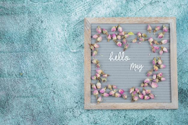 Ciao maggio frase incorporata su uno sfondo grigio con fiori in fiore intorno