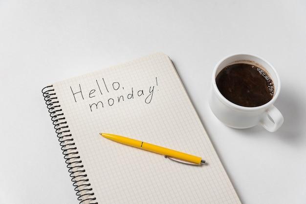 안녕하세요 월요일 동기 부여 통지. 메모장, 펜 및 화이트 커피 한잔.