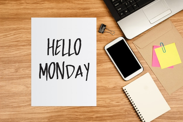 Hello monday text on white sheet and office supplies on wooden table