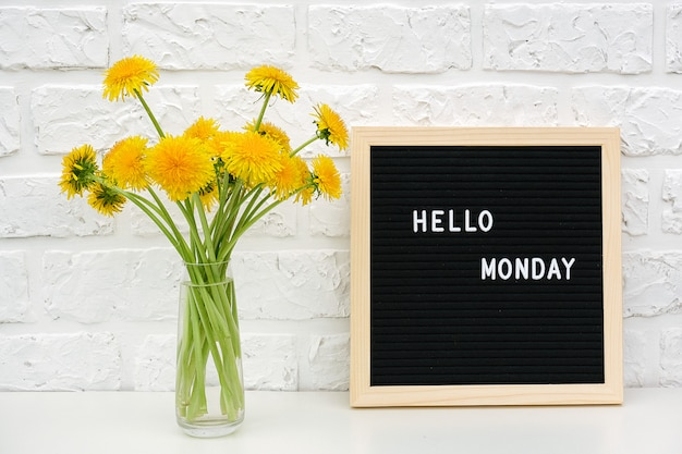 Hello monday words on black letter board and bouquet of yellow dandelions flowers