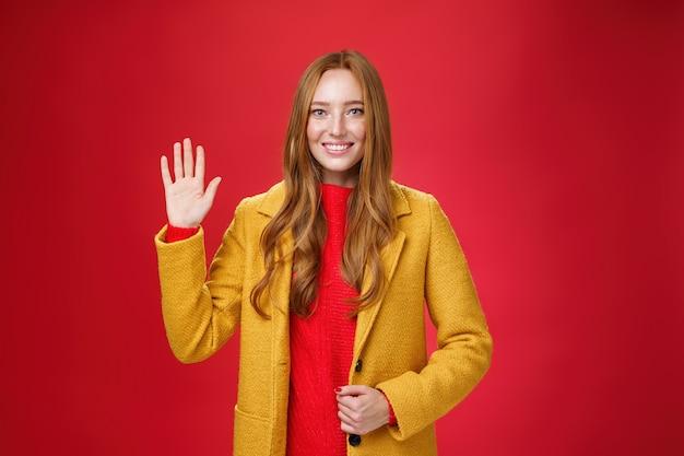 こんにちは、はじめまして。フレンドリーに見えるフェミニンでスタイリッシュな若いかわいい赤毛の女性は、黄色の暖かい秋のコートを着て、赤い壁の上で広く笑顔の挨拶とこんにちはジェスチャーで手を振っています。