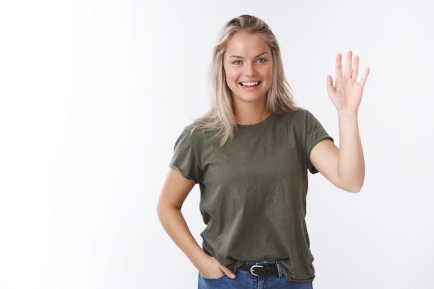 Привет! рад тебя видеть. портрет дружелюбно выглядящей очаровательной общительной женщины-коллеги со светлыми волосами, поднять ладонь и машет, приветствуя улыбающихся приятных, приветствующих гостей семинара, здороваясь