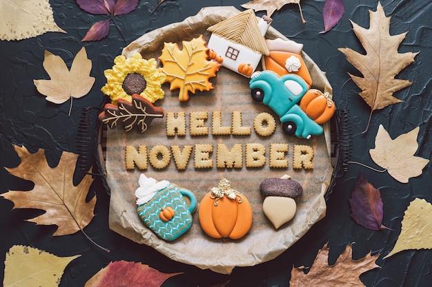 Привет, ноябрь. разноцветное осеннее печенье на черном фоне. осенняя концепция