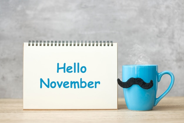 Hello november with paper notepad, blue coffee cup or tea mug and black mustache decor on table. international men day, happy father day and celebration concept