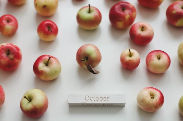 Привет октябрьская осенняя открытка со свежими красными яблоками на белом фоне, вид сверху