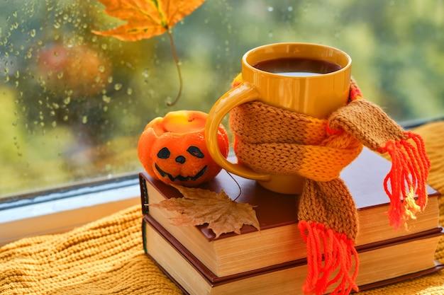 Привет октябрь. фон с книгами, чашка чая, свеча в форме тыквы, листья на подоконнике, за окном идет дождь