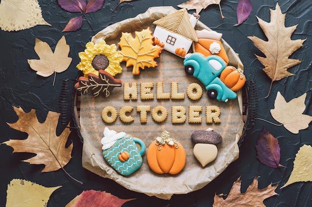 Привет октябрь. разноцветное осеннее печенье на черном фоне. осенняя концепция