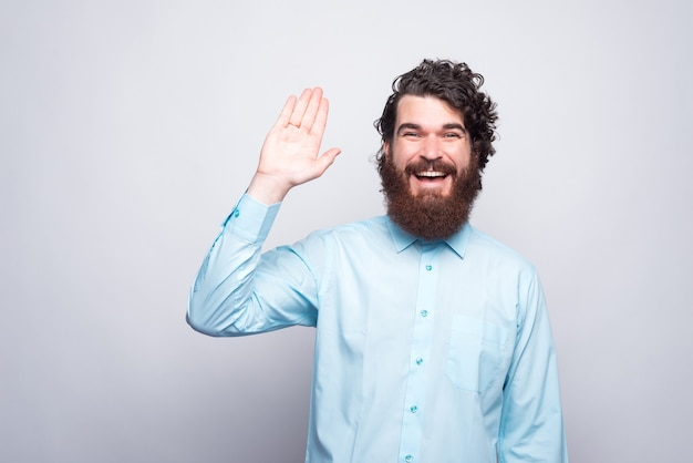 Hello people, smiling bearded man in casual saluting gesture.