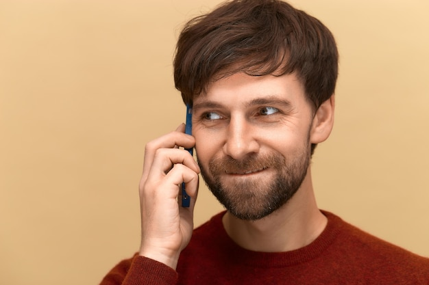 Hello. photo of young man wearing sweater, talking on mobile phone with his family, posing against beige wall