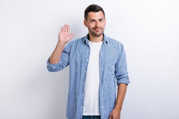 여보세요! 수염을 기른 선량한 남자의 초상화가 손을 흔들고 카메라를 향해 친절한 미소를 짓고 환영 제스처를 취합니다. 흰색 배경에 고립 된 실내 스튜디오 촬영