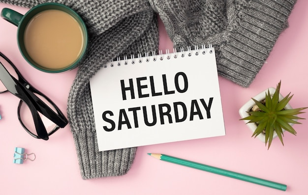 Hello saturday card with blooming flower on wooden background.