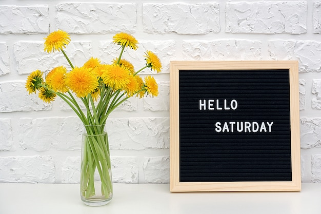 Hello saturday words on black letter board and bouquet of yellow dandelions flowers on table against white brick wall