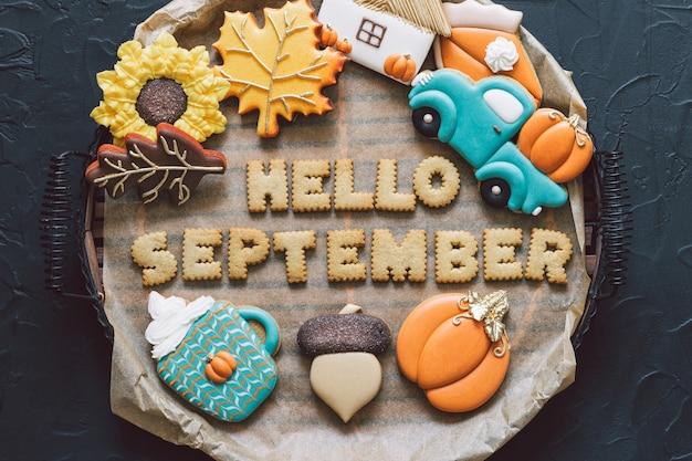 Привет, сентябрь. разноцветное осеннее печенье на черном фоне. осенняя концепция