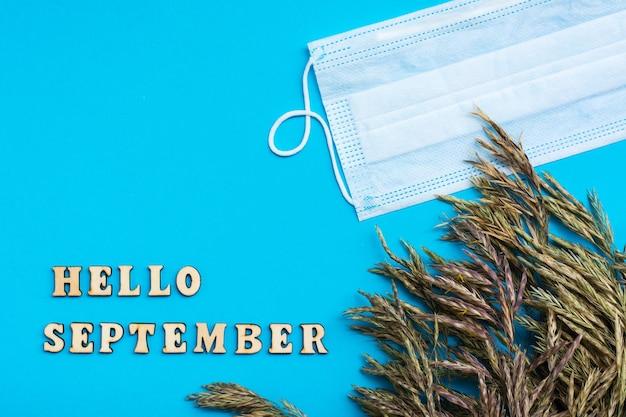 Привет сентябрь текст деревянными буквами и колосья травы с защитной маской