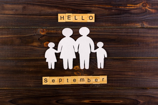 Hello september word with paper silhouette of family.