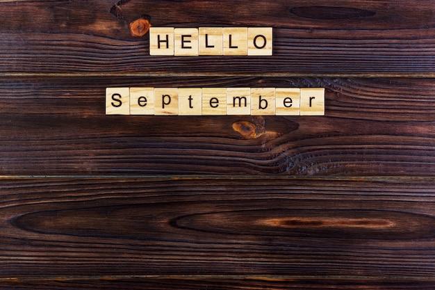 こんにちは、9月の言葉。木製の背景に木製キューブ
