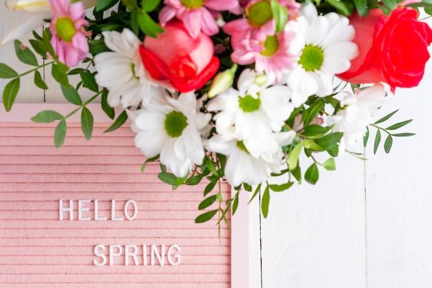 こんにちは春。白い背景に咲く花で作られたボーダーフレーム。