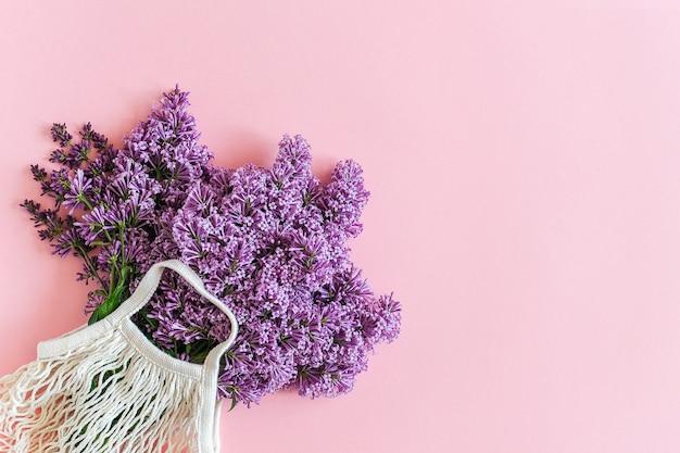 Hello spring. bright bouquet of lilac in white reusable shopping eco mesh bag concept no plastic, zero waste.