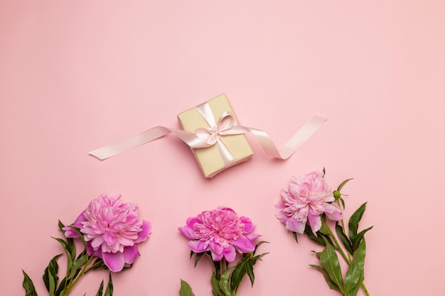Hello spring. creative floral composition of peonies and gift on white and pink table
