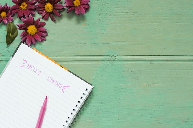 Hello spring inscription in notebook with flowers