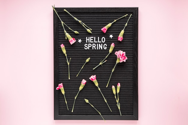 Hello spring inscription with flowers on black board