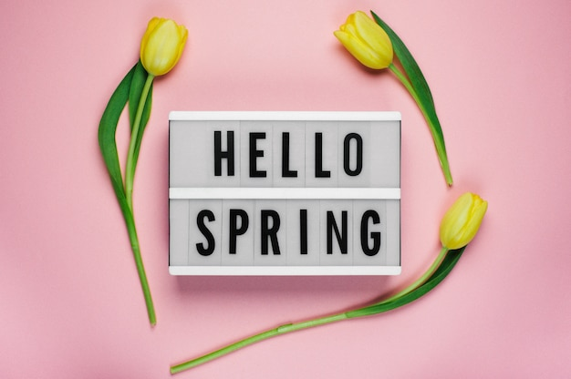 Hello spring - text on a display lightbox with yellow  tulips on pink .