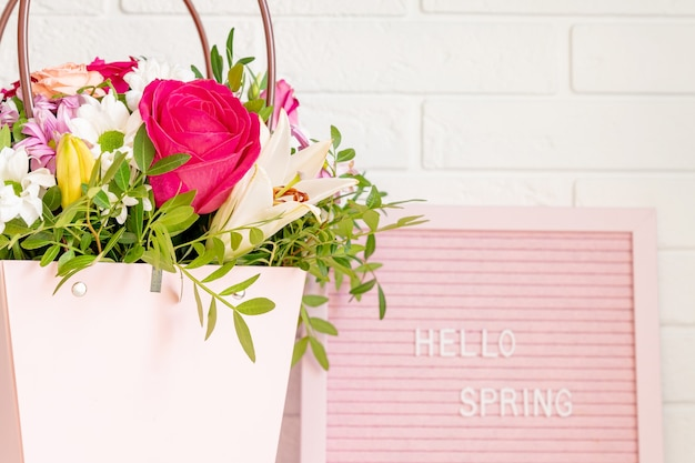 Hello spring - text on pink felt letter board with blooming flowers and green leaves on whitebrick wall background.