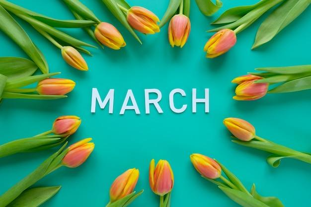 こんにちは、ミントの背景に新鮮な黄赤色のチューリップで春。国際女性の日、母の日、イースターの概念