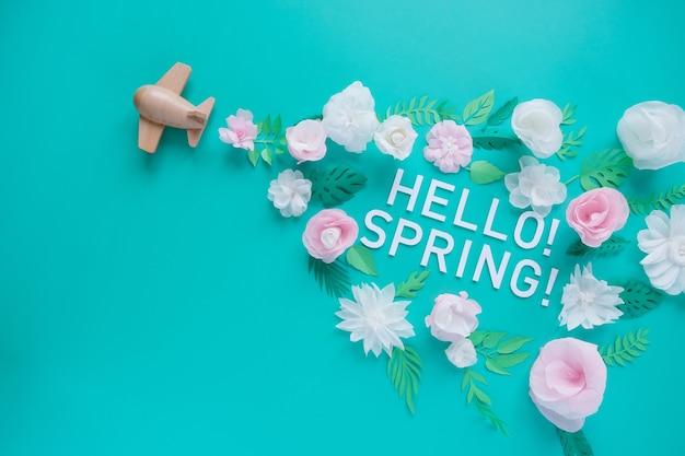 안녕하세요, 봄. 나무 장난감 비행기 행운 흰색과 분홍색 꽃 종이에서 잘라. 봄과 여행의 개념