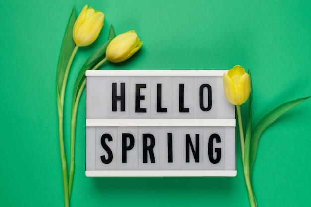 Hello spring - текст на лайтбоксе с желтыми тюльпанами на зеленом фоне.