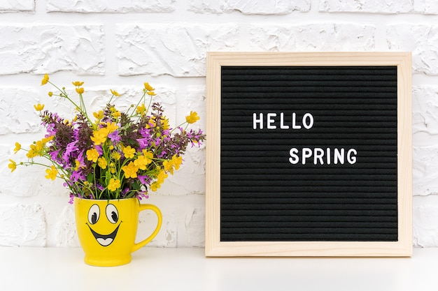 Текст hello spring на черной доске для писем и букет разноцветных цветов в забавной желтой чашке