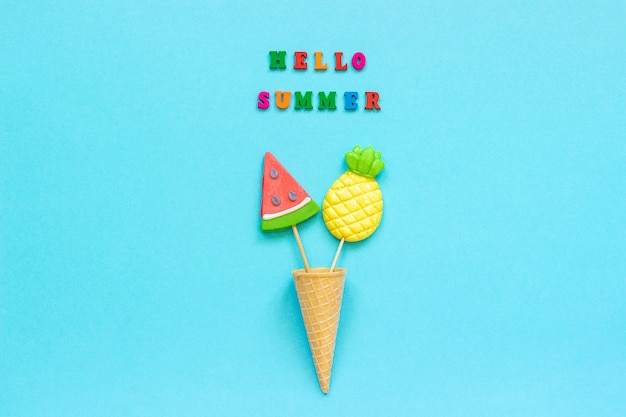 Hello summer colorful text, pineapple and watermelon lollipops in ice cream cone.