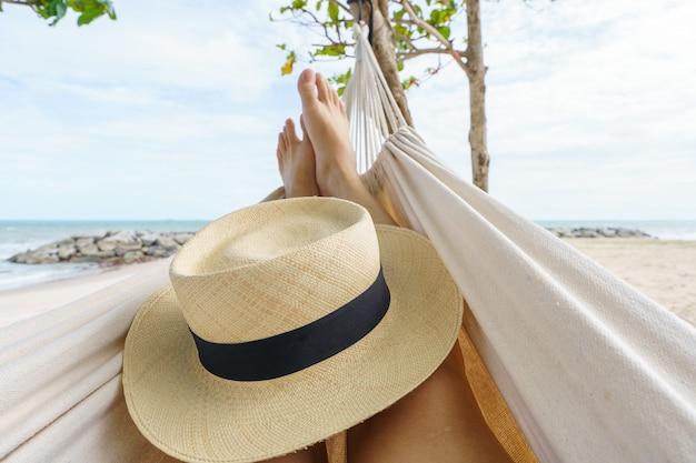 こんにちは夏休みの間にビーチで幸せな日光浴で日焼けハンモックでリラックスした夏の男。熱帯の休暇に。