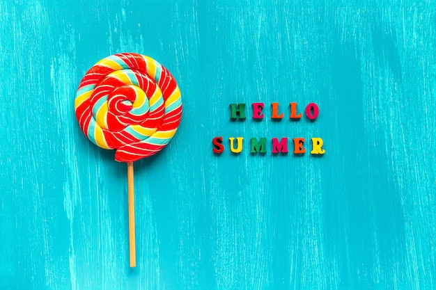 Hello summer text and spiral multi-colored round lollipop on stick on wooden blue background.