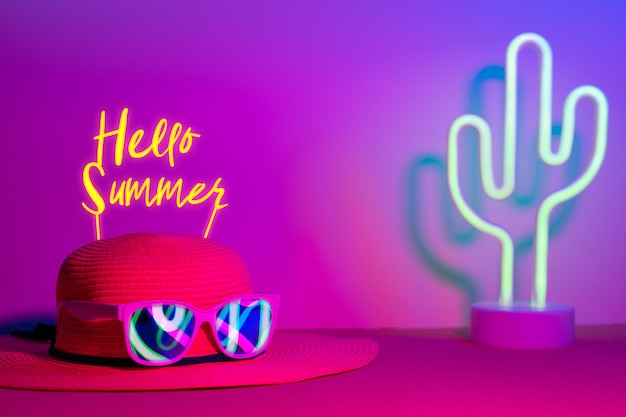Hello summer with hat and sunglasses refection neon light with cactus on  pink and blue on table