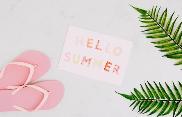 Бумага с сообщением hello summer и шлепанцы