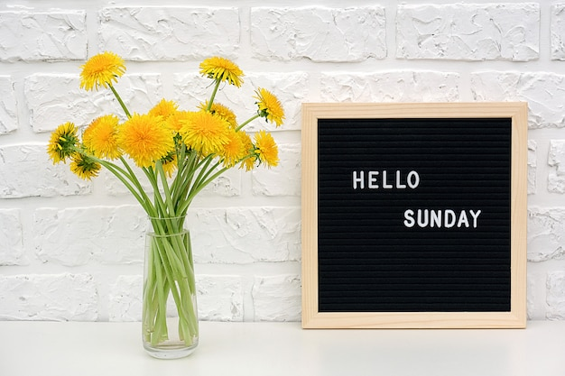 Hello sunday words on black letter board and bouquet of yellow dandelions flowers on table