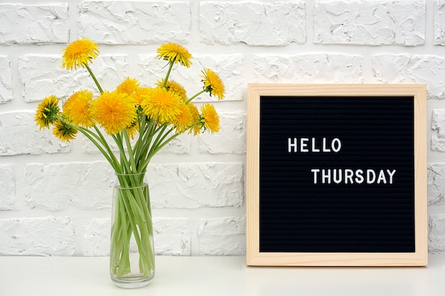 Hello thursday words on black letter board and bouquet of yellow dandelions flowers on table against white brick wall.