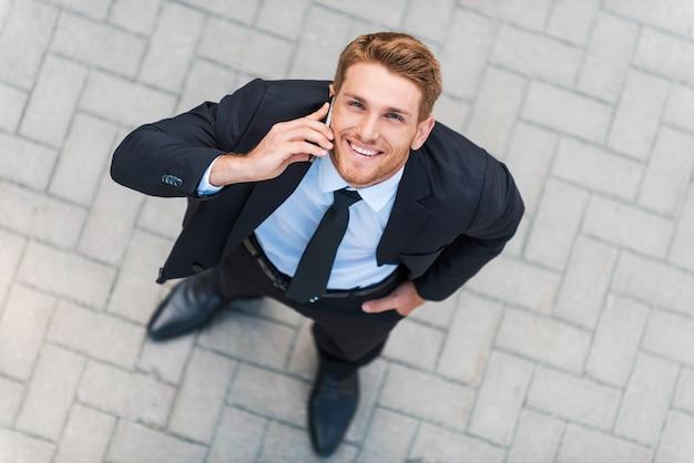 여보세요! 야외에 서있는 동안 휴대 전화로 이야기하고 웃는 formalwear에서 행복 한 젊은 남자의 상위 뷰