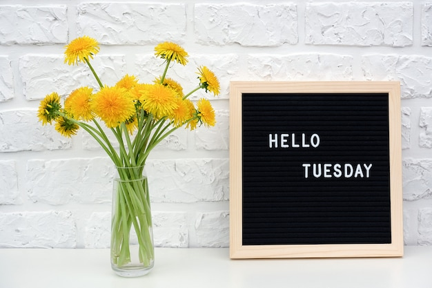Hello tuesday words on black letter board and bouquet of yellow dandelions flowers